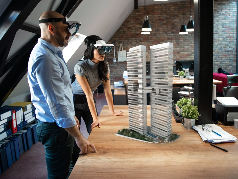Two people looking at 3d object by using AR glasses.
